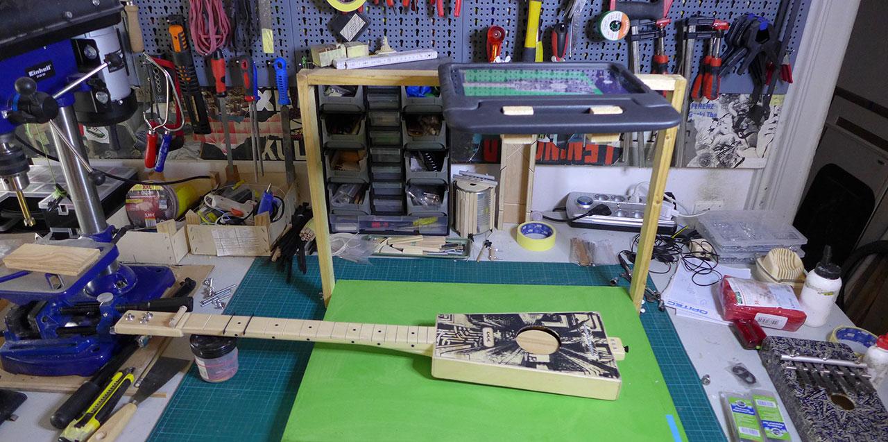 Ein Blick in meine unaufgeräumte Werkstatt mit DIY-Gitarre, Tablet und Trickfilmbühne.